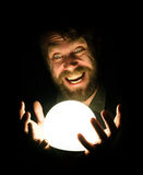 Close-up of a bearded man expresses various emotions on a black background, holding a lamp in front of himsalf Stock Photography