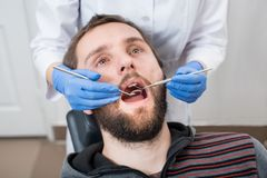 Close up of bearded man having dental check up in dental clinic Royalty Free Stock Image
