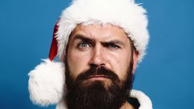 Close-up of bearded man in a new-year hat that raises eyebrows on blue background. New Year`s Concept. Santa move his. Eyebrows on blue background stock video footage