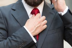 Close up of bearded man touching red tie while talking on the phone royalty free stock photography