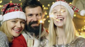 Close up of a bearded man and two blond girls which burn Bengal lights. New Year party. New Year mood. Christmas. Atmosphere, cozy mood stock video