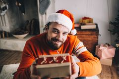 Portrait of attractive man before christmas. Close up of a bearded nice and cheerful guy sitting on the floor and presenting a gift that he packed by himself stock images