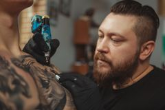Bearded tattooist making tattoos on body of his client. Close up of a bearded professional tattoo artist looking focused, tattooing male client on the chest stock image