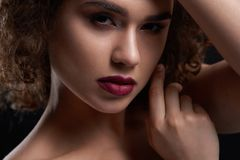 Close up of beatiful curly girl. Original close up of beatiful curly girl with pretty appearance. Wearing bright lipstick and light day make up. Model posing on royalty free stock photo