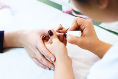 Close-up of beautician applying colorful varnish Stock Photos