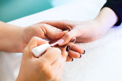 Close-up of beautician applying colorful varnish Royalty Free Stock Photos