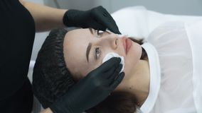 Close up beautician cleans skin of woman face before procedure, slow motion. Girl in beauty salon stock footage