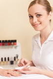 Close-up of beautician hand filing nails of woman in salon. Stock Images