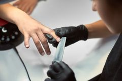 Close-up of beautician hands in black gloves filing client woman nails in shape using emery board. stock image