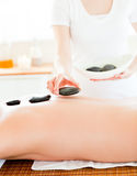 Close-up of a beautician putting hot stones Stock Image