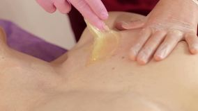 Beautician removes hair from the mans chest with sugar paste. Sugaring. Close-up beautician removes unwanted hair from the mans chest using sugar paste in the stock footage