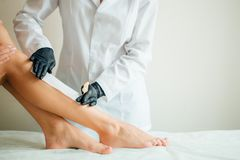 Close-up Of A Beautician Waxing Woman Leg With Wax Strip At Beauty Spa. Close up Beautician waxing a woman`s leg applying a strip of material over the hot wax to Royalty Free Stock Photo