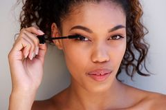 Close up beautiful african american woman putting on make up. Close up horizontal portrait of beautiful african american woman putting on make up Stock Images