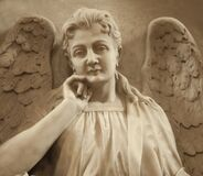 Close up of beautiful angel with wings. Ancient stone statue, fragment