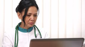 Close up of a beautiful Asian female mature doctor working on her laptop royalty free stock photo