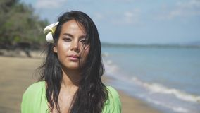 Close-up of a beautiful asian girl walking along the beach in a green dress. With a tropical flower in her hair. Thailand stock footage