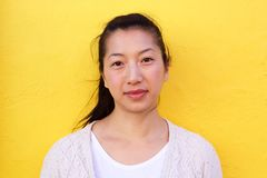 Close up beautiful asian woman against yellow wall Royalty Free Stock Photography