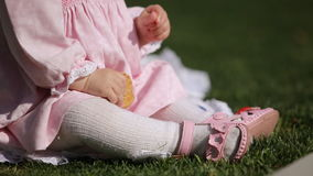 Close-up of the beautiful baby-girl seating on the green grass in the park. stock video