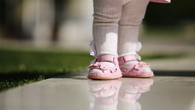Close-up of the beautiful baby-girl standing in the park at sunlight day. stock video footage
