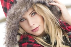 A close-up of a beautiful blond woman with piercing blue eyes in plaid fur hood. A close-up of a beautiful blond woman with piercing blue eyes wearing a red and Royalty Free Stock Images