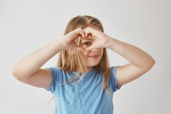 Close up of beautiful blonde girl making heart with hands, looking through it in camera, posing for photo with smile and. Happy expression royalty free stock photography
