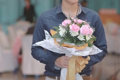 Close up beautiful bouquet of flower for his girlfriend with handsome young Asian man.  Sweet valentine`s day or wedding concept. Royalty Free Stock Photography