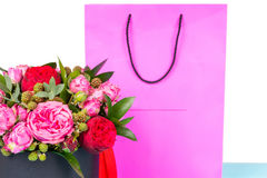 Close up of beautiful bouquet of pink and red roses and red ribb. On in a circular black box near pink gift bag. Valentines and anniversary concept Royalty Free Stock Image