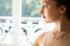 Beautiful bride wearing necklace looking through window at home Royalty Free Stock Image