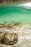 Close up of beautiful bronze rock in pure crystal clear green water Stock Photos