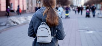 Close-up of a beautiful brunette girl with long hair in a coat goes around the city in spring, view from behind Royalty Free Stock Photo