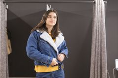 Closeup of brunette in a shop trying on a denim jacket with a collar stock photo