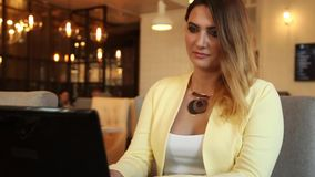 Close-up. Beautiful business woman typing text on a mobile computer sitting at a table in a cafe having a good mood. HD. Close-up. Beautiful business woman with stock footage