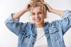 Close-up beautiful carefree friendly-looking outgoing blond woman curly hair combed bun touching head joyfully enjoying stock photos