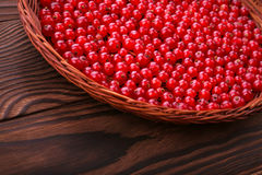 Close-up of a beautiful composition of a light wooden basket with fresh red currant on a wooden background. Red berries in the box. A light wooden basket full of stock photography