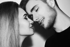 Close-up of beautiful couple kissing. Happy man and girl touching with their noses. Black and white. Close-up of beautiful couple kissing. Happy men and girl Stock Images