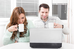Close up beautiful couple working on laptop at home. Close up beautiful couple working and looking on laptop at home with a cup in hands drinking tea or coffee stock photo
