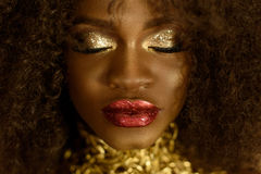 Close up of beautiful elegant african american woman. Girl posing with closed eyes and jewelry, wearing fashionable gold necklace Stock Photo
