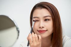 Close up of beautiful face of asian young woman getting make-up. Asian woman is applying eyeshadow on her eyebrow with brush. Beautiful girl look at mirror royalty free stock photo