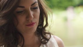 Close-up beautiful face of dreamy brunette curled woman artist with pencil in hands on the plener outdoor the forest.  stock video footage
