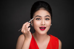 Close up of beautiful face of young asian woman applying eyeshad Stock Photo