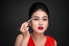 Close up of beautiful face of young asian woman applying eyeshad. Ow on her eyebrow with brush Royalty Free Stock Photos