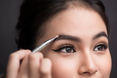 Close up of beautiful face of young asian woman getting make-up. Royalty Free Stock Image