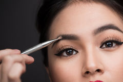 Close up of beautiful face of young asian woman getting make-up. The artist is applying eyeshadow on her eyebrow with brush royalty free stock image