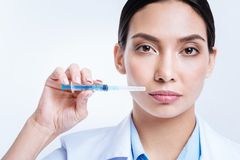 Close up of beautiful female doctor holding a syringe stock photos