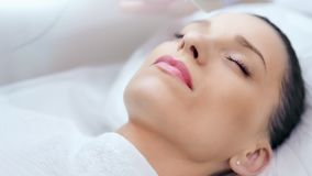 Close-up beautiful female face enjoying beauty ultrasonic cleansing procedure at clinic stock video