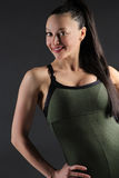 Close up of a beautiful female fitness model with her hand on her side. Image of a fit woman smiling wearing a green all in one outfit on a dark background Stock Images
