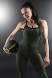 Close up of a beautiful female fitness model holding a gym ball on her side Royalty Free Stock Images