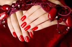 Close up on beautiful female hands with sexy red manicure. Stock Photo
