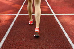 Close up on beautiful female legs with pink shoes on the running track Stock Photography