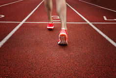 Close up on beautiful female legs with pink shoes on the running track Royalty Free Stock Image